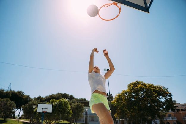 Female teen student playing basketball at sportsground