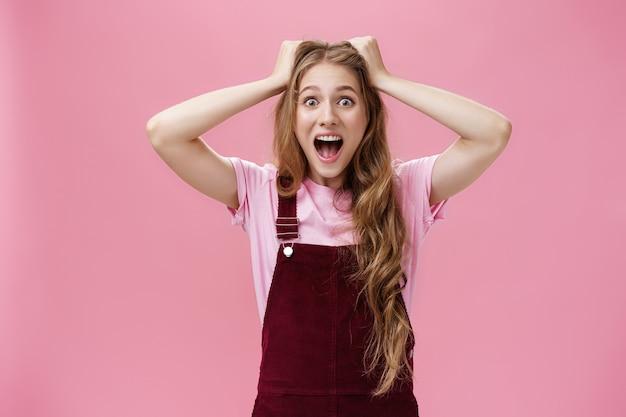 여자 10대 여성은 좋아하는 밴드 콘서트에서 머리에 손을 얹고 놀라움과 분홍색 배경에 과민 반응하는 놀라움으로 비명을 지르며 흥분한 기분을 진정시킬 수 없습니다.