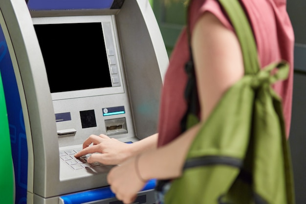 Female teenager carries green bag, wants to withdraw cash, stands near atm machine, enters pin, makes payment