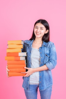 Female teenager holding stack of book on pink