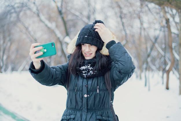 冬のシーズン中に雪の公園を歩いて女性10代