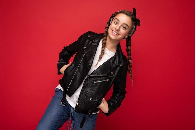 カメラを見て赤い背景の壁の上に分離されたスタイリッシュな黒い革のジャケットと白いtシャツを身に着けているおさげ髪の女性のティーンエイジャー。