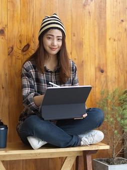 Девушка-подросток работает с цифровым планшетом на коленях, скрестив ноги, сидя в кафе
