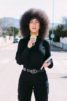 Female television reporter journalist with afro hair reporting on a news story on the street