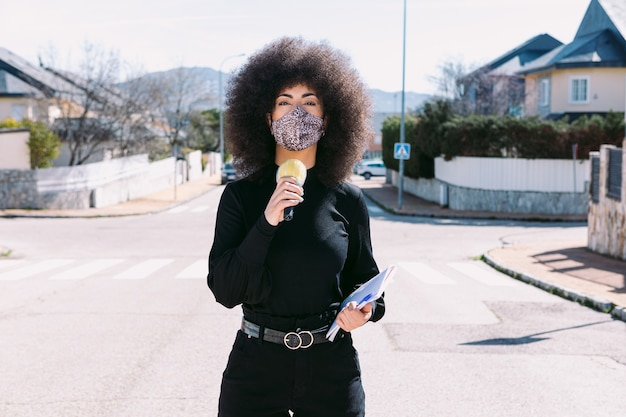Female television reporter journalist with afro hair, wearing a leopard skin mask to protect herself from a virus, reporting on a story on the street