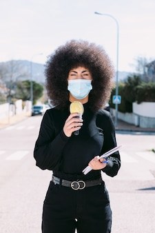 Female television reporter journalist with afro hair, wearing a surgical mask to protect herself from a virus, reporting on a story on the street