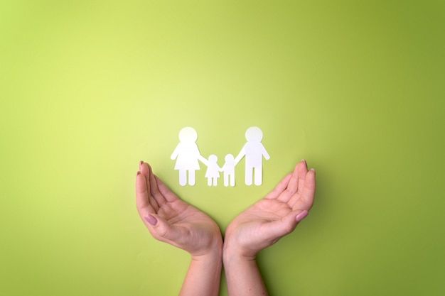 Female tender hands with a family symbol cut out of white paper. protecting the rights of people and sexual minorities.