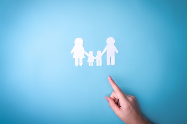 Female tender hands with a family symbol cut out of white paper. protecting the rights of people and sexual minorities