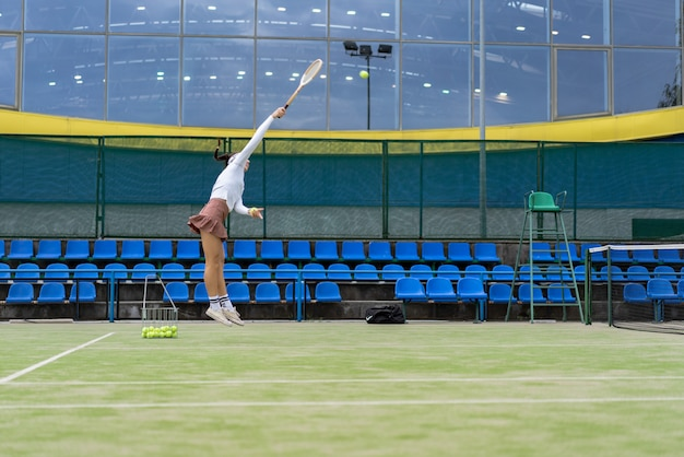 Female tennis player on green court grass