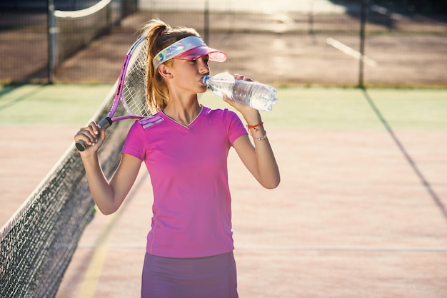 일몰에 야외 코트에서 테니스 훈련 후 플라스틱 병에서 분홍색 유니폼 식 수에 여자 테니스 선수.