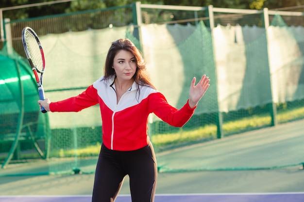 スポーツウェアの女性テニスプレーヤーがトレーニングでテニスをします。