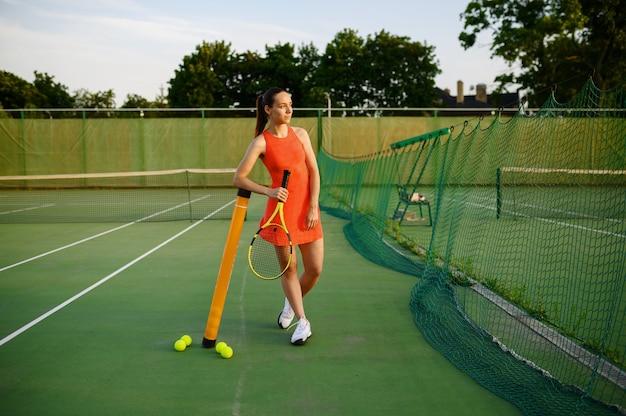 スポーツウェアの女性テニスプレーヤーが屋外コートのネットでポーズをとる