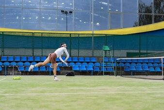 Female tennis player on green court grass