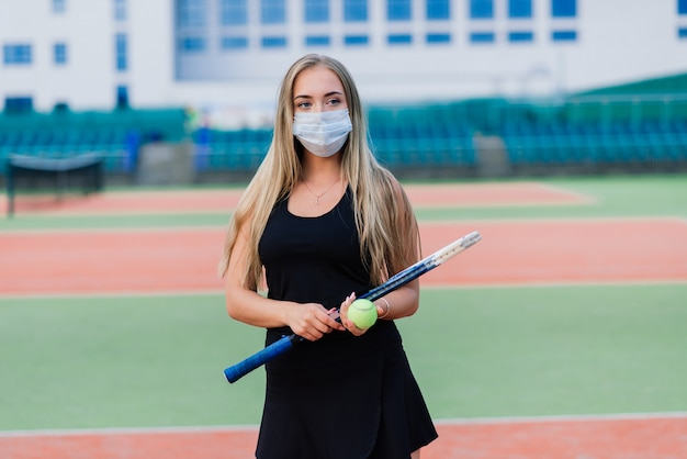 Female tennis player playing with protective mask on court