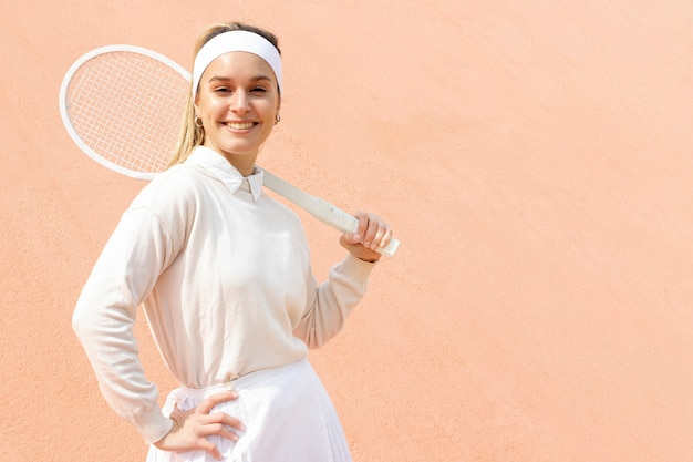 Female tennis player posing with racket