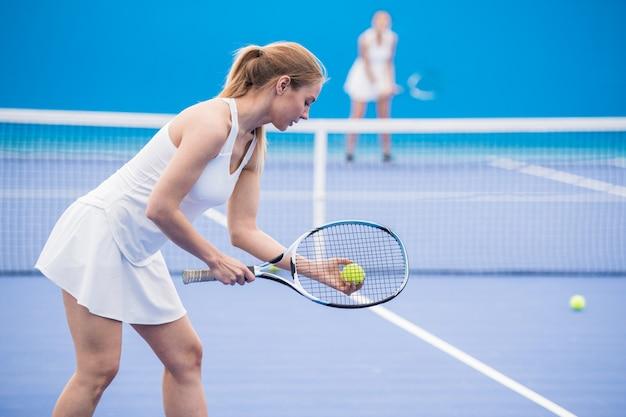 試合でサービングの女子テニス選手