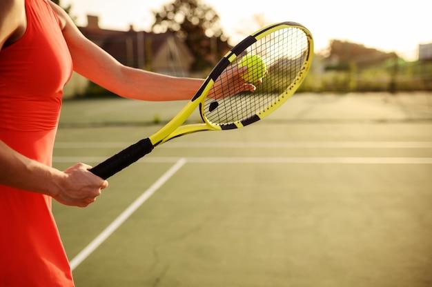 屋外コートでラケットとボールを持つ女性のテニスプレーヤー。アクティブで健康的なライフスタイル、スポーツゲームの競争、ラケットを使ったフィットネストレーニング