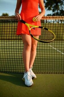 屋外コートのネットでラケットとボールのポーズを持つ女性テニスプレーヤー