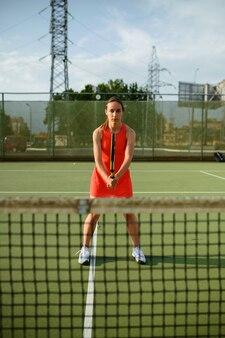 屋外コートのネットでラケットを持った女性テニスプレーヤー。アクティブで健康的なライフスタイル、スポーツゲームの競争、ラケットを使ったフィットネストレーニング
