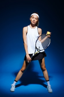 Female tennis player with racket and ball in hand posing