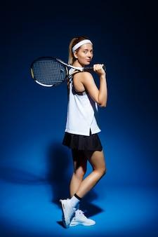 ポーズの肩にラケットを持つ女性のテニス選手
