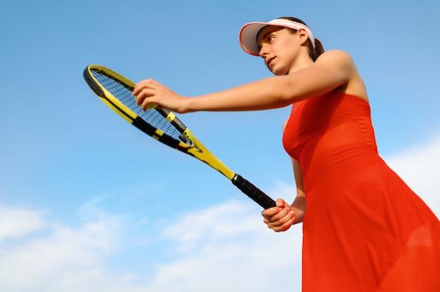 ラケットを持った女性テニスプレーヤーが屋外コートでボールを打つ準備をしています。アクティブで健康的なライフスタイル、スポーツゲームの競争、ラケットを使ったフィットネストレーニング