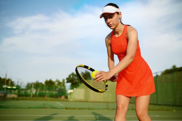 ラケットを持った女性テニスプレーヤーが屋外コートでボールを打つ準備をしている
