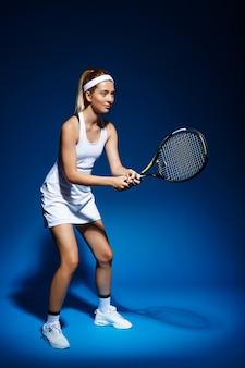 Tennis femminile con la racchetta pronta a colpire una palla.