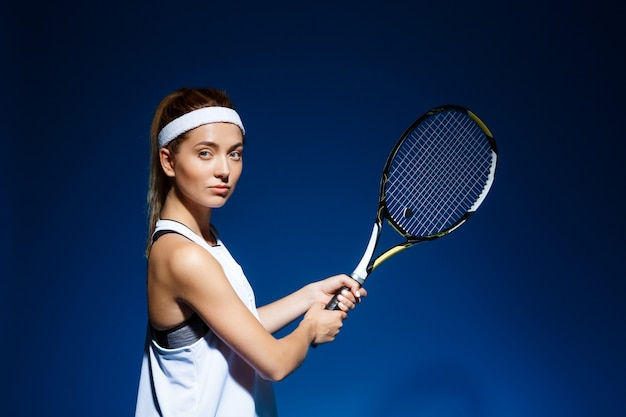 Теннисистка с ракеткой готова ударить по мячу.