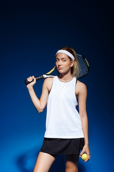 Female tennis player with racket on the shoulder