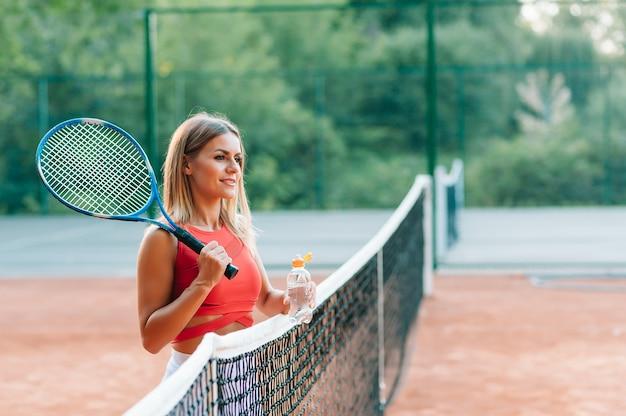 Теннисистка с полотенцем на плечах пьет воду после матча Premium Фотографии