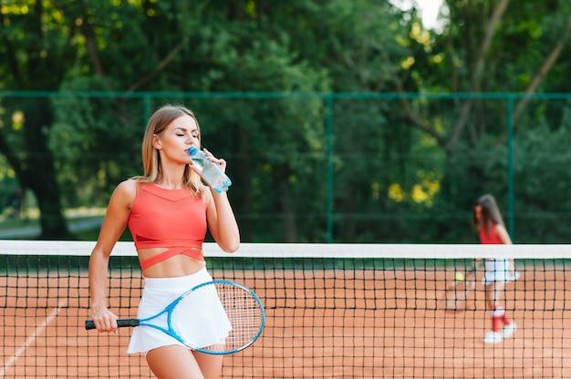 Теннисистка с полотенцем на плечах пьет воду после матча