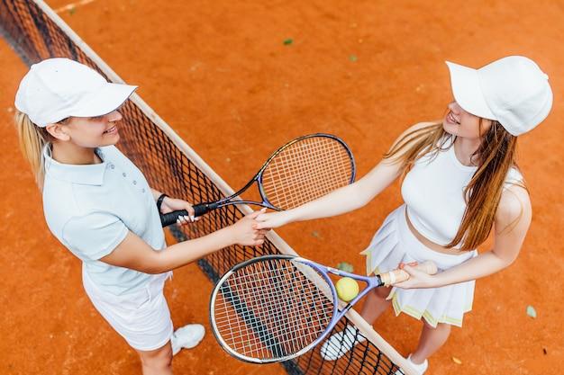 여자 파트너와 함께 클레이 코트에서 카메라를 보고 행복해 보이는 여성 테니스 선수.