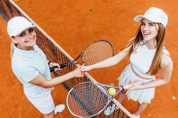 Female tennis players looking happy at  camera on clay court with woman partner.