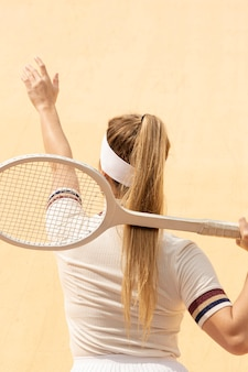 Female tennis playes back with racket