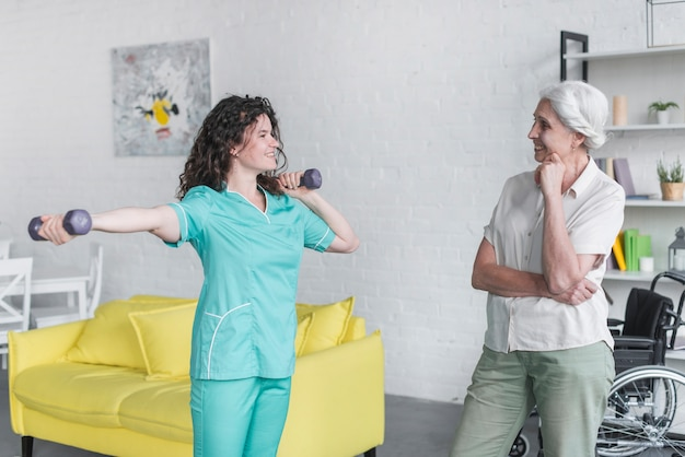 Female therapist assisting senior woman with dumbbells