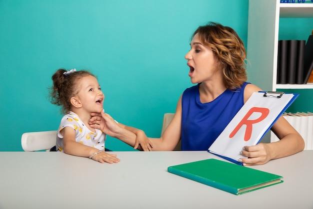 白いキャビネットで発音に問題のある子供と一緒に働く女性セラピスト。