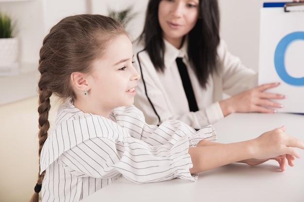 흰색 캐비닛에서 발음에 문제가 있는 아이와 함께 일하는 여성 치료사.