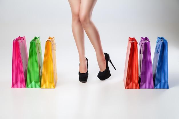 Женские тонкие ножки с цветными сумками