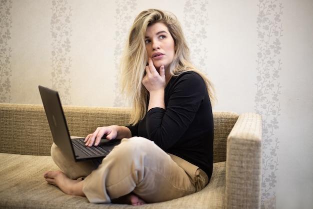 그녀의 무릎에 노트북으로 생각하는 여성