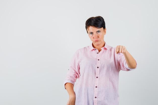 핑크 셔츠에 주먹으로 위협하고 엄격한 여성. 전면보기.