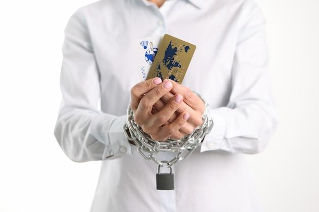 プラスチック製のクレジットバンクカードで女性の縛られた手はローンと銀行に依存している