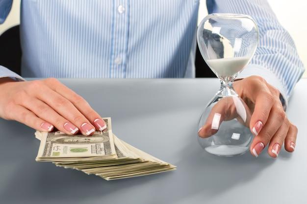 여성은 현금과 모래시계를 만집니다. 모래 시계와 돈을 만지는 여자. 둘 다 즐겨보세요. 두 개의 다른 경로입니다.