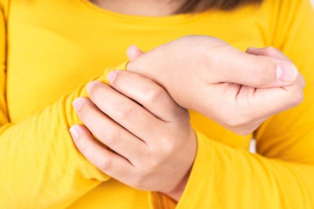Женщина трогает ее боль в запястье.