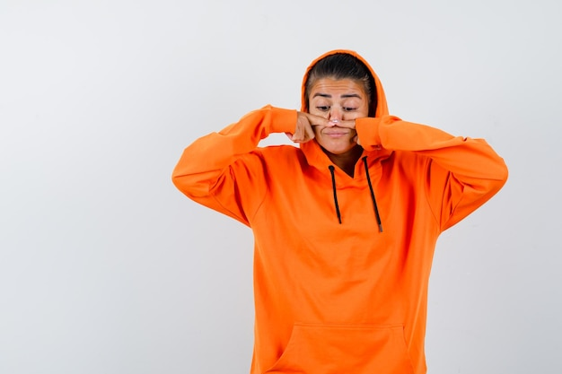 Женщина трогает нос пальцами в оранжевой толстовке с капюшоном и выглядит смешно