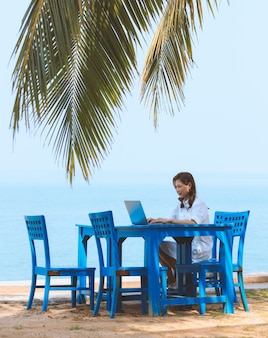 Женский туризм сидит за синим столом рядом с песчаным пляжем с листьями кокосовой пальмы и использует портативный компьютер для работы в интернете.