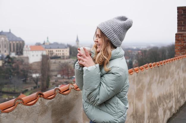 Туристка на фоне города в чехии - кутна гора. она пьет глинтвейн - осенний сезон
