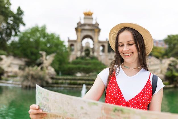 バルセロナのシウタデラ公園を訪れながら地図をチェックする女性観光客