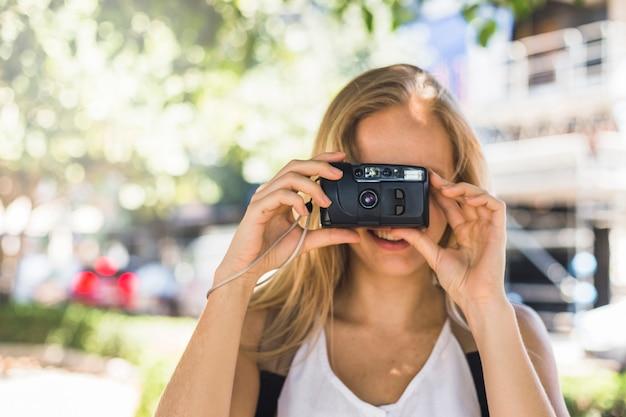 Female tourist clicking photos through digital camera at outdoors Free Photo