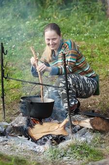 Женский турист, готовящий пищу в котле